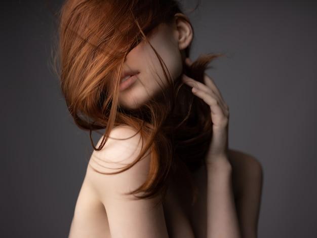 Женщина с голыми плечами, рыжими волосами, позирует с чистой кожей. фото высокого качества
