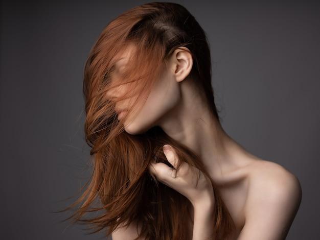 透明な肌をポーズする裸の肩の赤い髪の女性