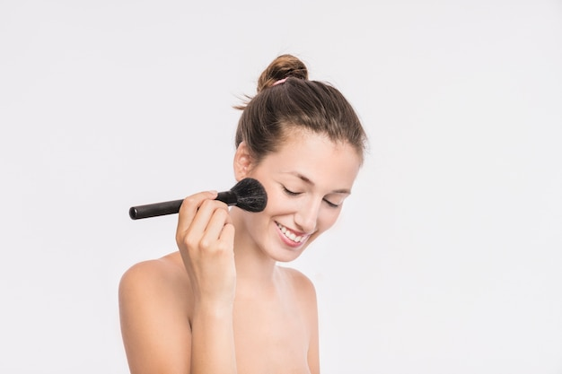 Woman with bare shoulders using powder brush