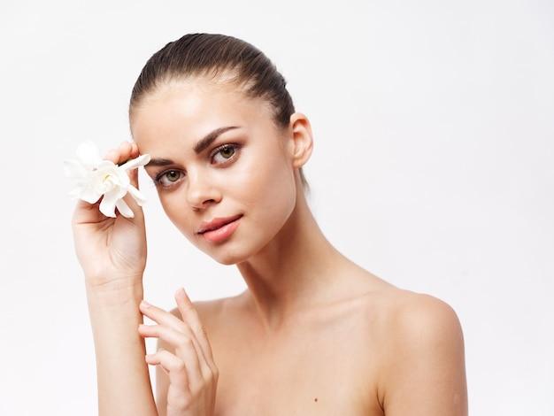 裸の肩を持つ女性白い花きれいな肌の化粧品