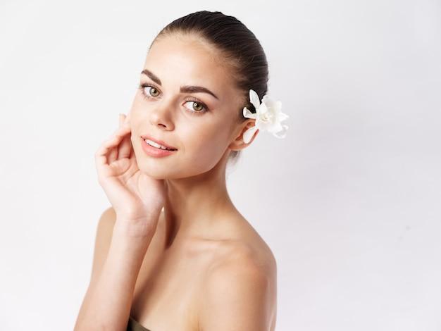 裸の肩を持つ女性白い花の顔メイクチャーム明るい背景