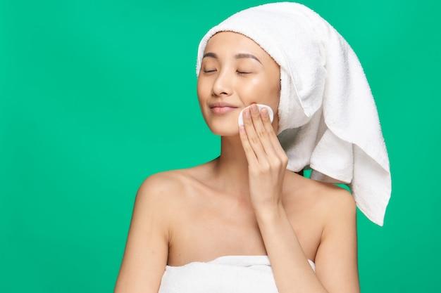 맨 손으로 어깨를 가진 여자는 메이크업 녹색 배경 후 그녀의 얼굴을 닦지 만 면봉으로