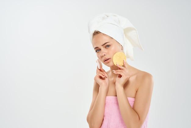 顔の皮膚を掃除する彼女の頭にタオルで裸の肩を持つ女性
