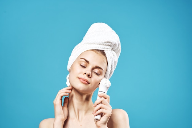 Женщина с обнаженными плечами с полотенцем на голове, уход за массажером для лица