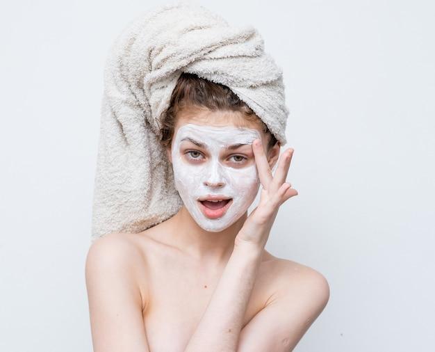 彼女の頭のスキンケアフェイシャルマスクにタオルで裸の肩を持つ女性。
