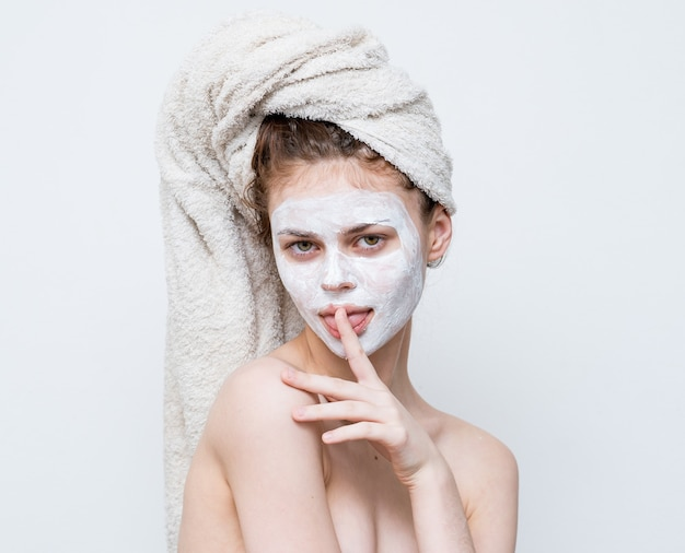 Женщина с голыми плечами с полотенцем на маске ухода за кожей головы.