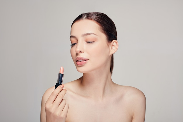 Woman with bare shoulders with lipstick in her right hand looks at her lipstick with a full lips