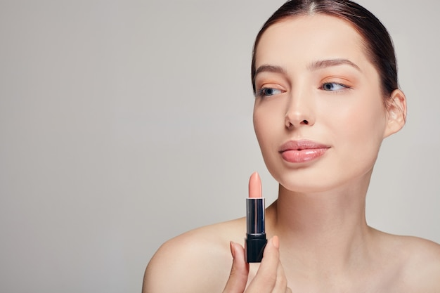 Woman with bare shoulders with lipstick in her right hand looks at side with a full lips and blue eyes