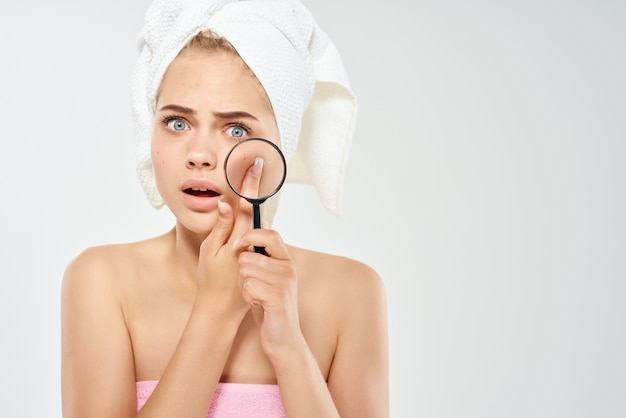 Woman with bare shoulders with towels talking skin problems magnifier near face