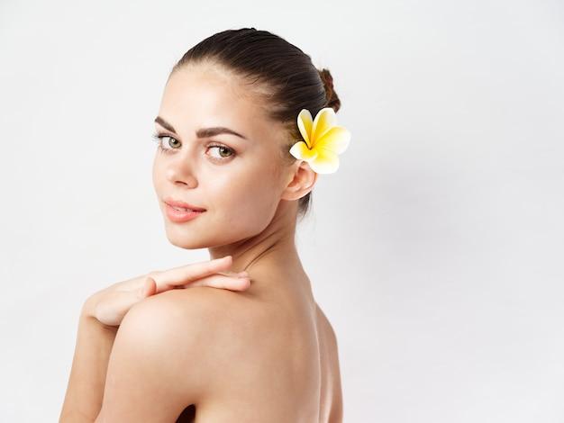 Женщина с голыми плечами желтый цветок за ухом прозрачная кожа
