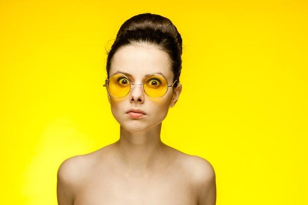 裸の肩を持つ女性黄色いメガネの感情