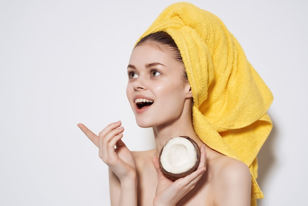 Женщина с голыми плечами, желтое полотенце на кокосовой голове, держит чистую кожу фруктов