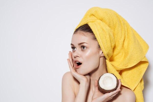 果物のきれいな肌を保持している彼女の頭のココナッツに裸の肩の黄色いタオルを持つ女性
