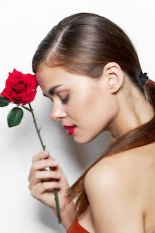 目を閉じて裸の女性彼は顔の肩の近くにバラを持っています