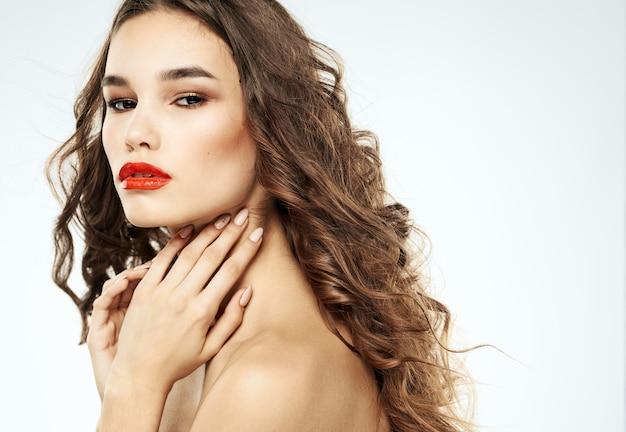 むき出しの肩の巻き毛の赤い唇のメイクの女性