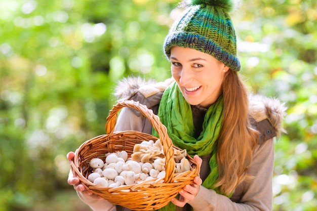 Woman with basket full of champignons in forest
