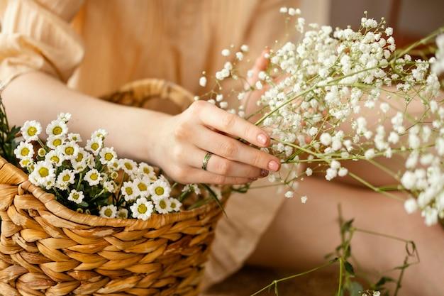 春の花のバスケットを持つ女性