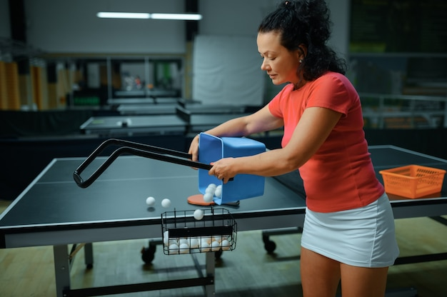 Woman with basket of ping pong balls, table tennis training in gym, female player