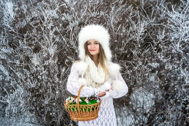 겨울 스노우 파크에서 바구니를 가진 여자
