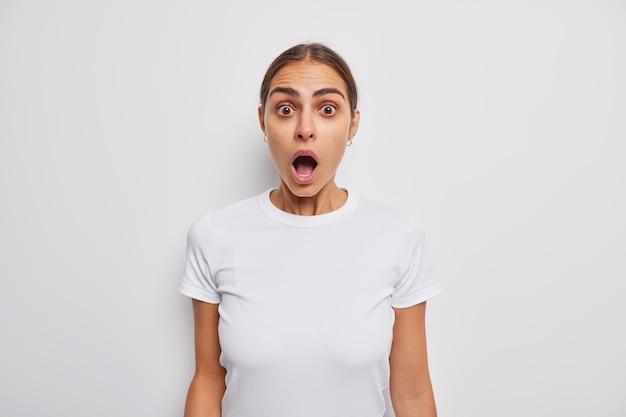 Женщина, затаив дыхание, держит рот широко открытым, не может поверить своим глазам, одетая в повседневную футболку на белом