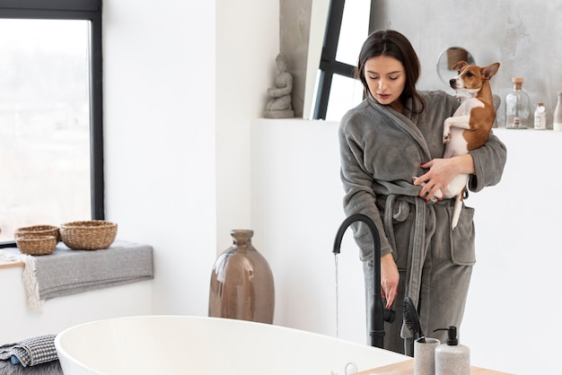 Woman with bathrobe holding dog while in the bathroom