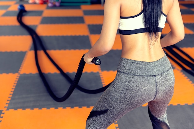 Woman with battle rope in functional training fitness,taking weight loss