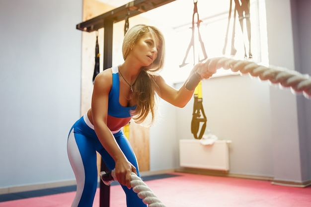 Woman with battle ropes exercise in the fitness gym. young female wearing sportswear.