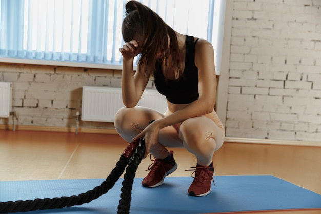 バトルロープを持つ女性は、フィットネスジムで運動します。アスリート、スポーツ、ロープ、トレーニング、トレーニング、エクササイズ、健康的なライフスタイルの概念