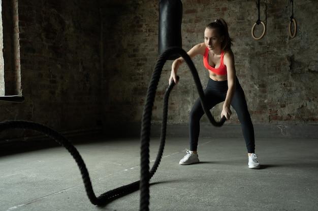 Женщина с боевыми канатами упражняется в фитнес-зале, спортсменка работает в тренажерном зале