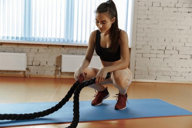 피트 니스 체육관에서 배틀 로프 운동을 가진 여자.