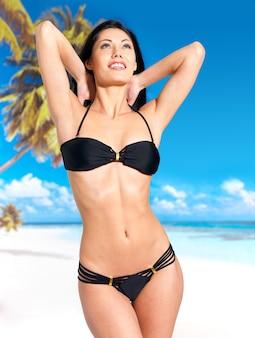 검은 비키니 입은 아름다운 몸매를 가진 여인이 해변에서 일광욕