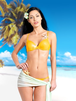 ビーチで黄色いビキニの美しい体を持つ女性