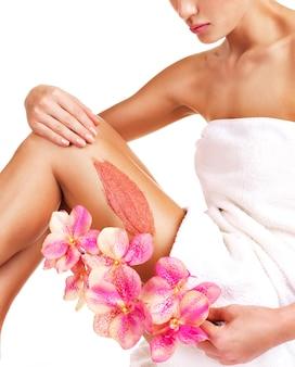 La donna con un bel corpo con fiore utilizzando uno scrub sulla gamba su un bianco