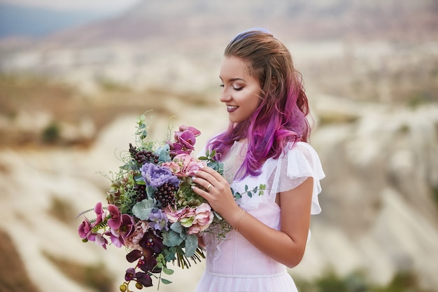 Woman with beautiful bouquet of flowers in hands stands on mountain in rays of dawn sunset. beautiful white long dress on the woman body. perfect bride with pink hair
