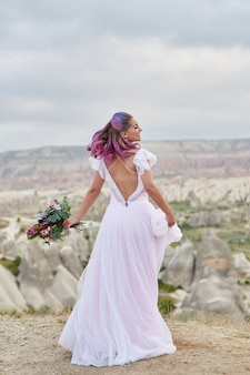 Woman with a beautiful bouquet of flowers in her hands dance on the mountain in the rays
