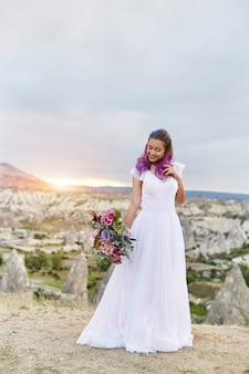 Woman with a beautiful bouquet of flowers in her hands stands on the mountain in the rays of the dawn sunset. beautiful white long dress on the girl body. perfect bride with pink hair