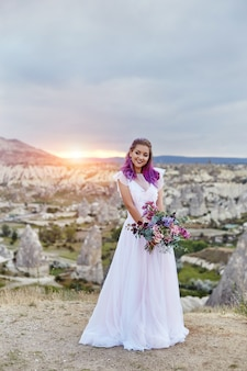 Woman with a beautiful bouquet of flowers in her hands stands on the mountain in the rays of the dawn sunset. beautiful white long dress on the woman body. perfect bride with pink hair