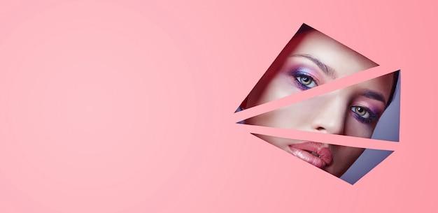 美しい明るい化粧とピンクの口紅を持つ女性は、ピンクの紙の三角形のスリットを通して見えます。広告化粧品、プロのアートメイク、リップグロス、明るい色。女の子は穴あき紙に見えます