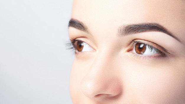 Woman with beautiful eyebrows close-up on a light background with copy space