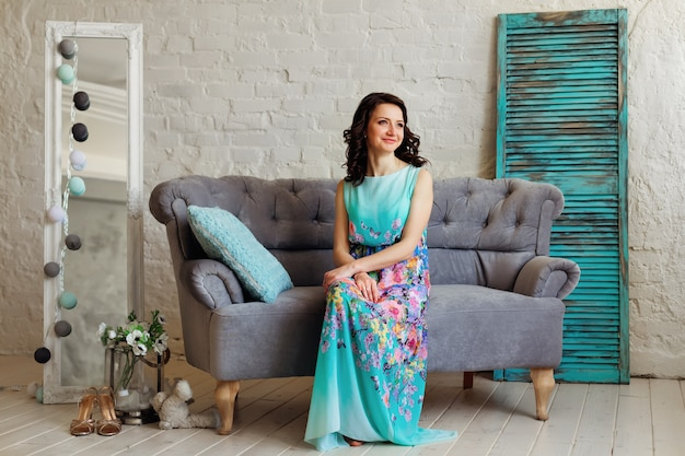 A woman with a beautiful hairstyle and a gentle dress is sitting on the couch in the room with decorations