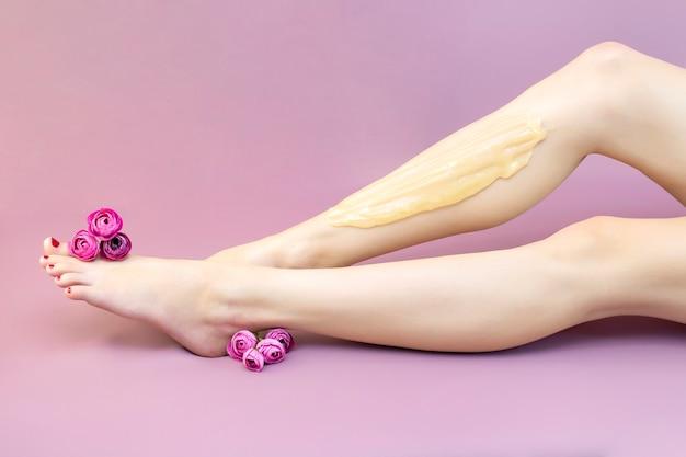 Женщина с красивыми ногами после депиляции на розовом