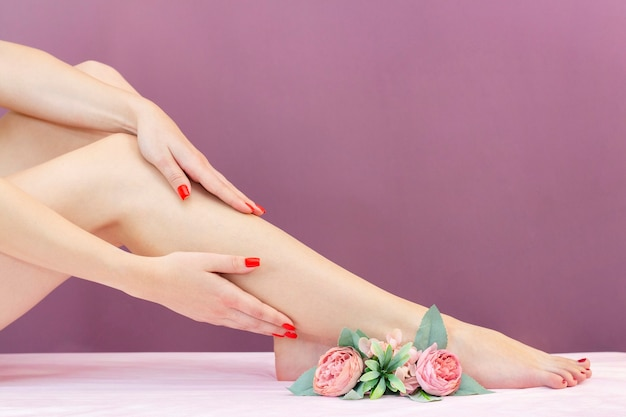 Woman with beautiful legs after depilation on pink background. sugaring