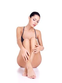 Donna con belle gambe in bikini si siede su sfondo bianco