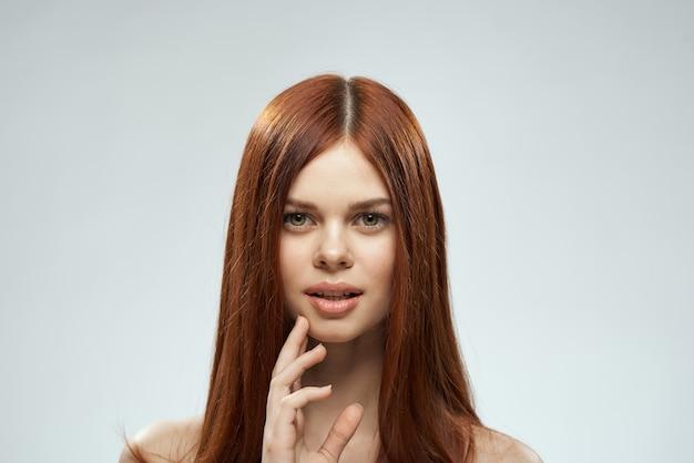 Женщина с красивыми длинными волосами, уход за обнаженными плечами, косметика, обрезанный вид, свет