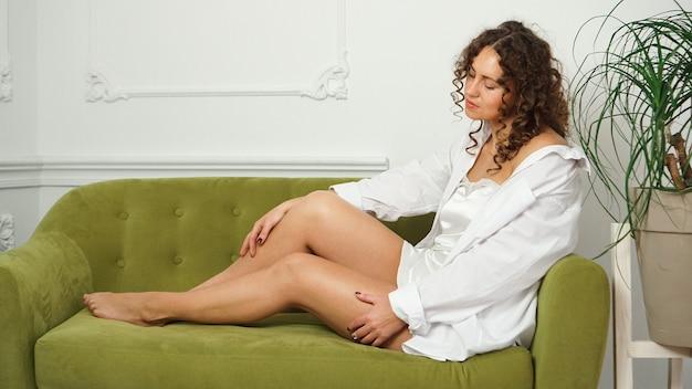 Женщина с красивыми длинными ногами на зеленом диване у себя дома