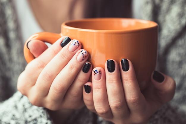 ココアのオレンジ色のカップを保持している美しいマニキュアを持つ女性
