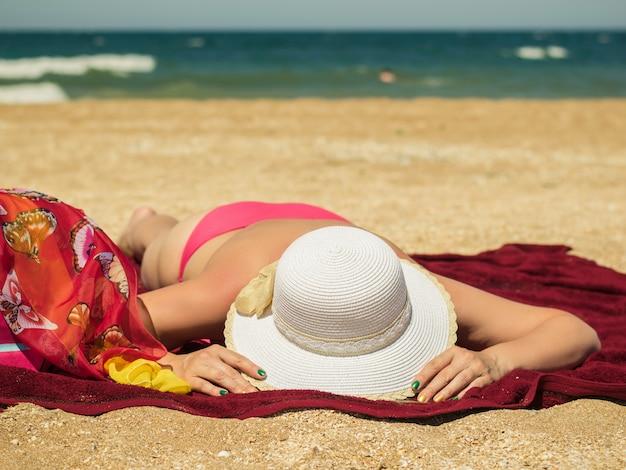 Женщина с красивые ногти, держа его шляпу, загорая на пляже у моря.