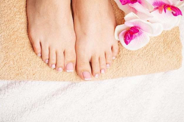 Woman with beautiful skin of feet and fresh manicure doing spa treatments for her feet.