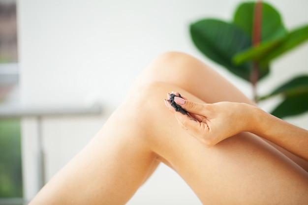 Woman with beautiful skin on her feet applies anti-cellulite scrub cream on her leg