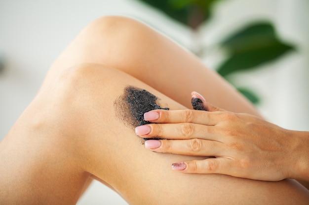 Женщина с красивой кожей на ногах наносит антицеллюлитный скраб-крем на ногу